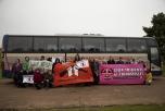 En grupp människor framför en buss med banderoller