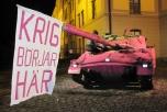 """Bild på rosamålad stridsvagn i Umeå med banderoll """"Krig börjar här"""""""