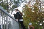 Bild på Karin Carlsson som klättrar över staketete till Aimpoint.