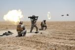 3 soldater i en öken avfyrar en Carl Gustaf-raket