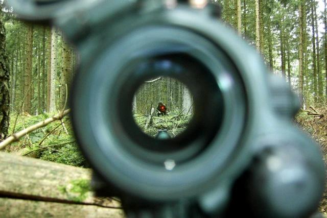 Soldat fotad genom ett sikte, med en röd punkt på kroppen