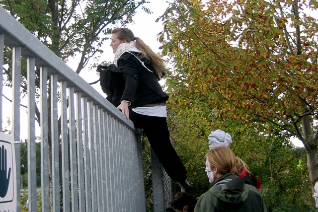 Bild när Karin Carlsson klättrar över en gallergrind.
