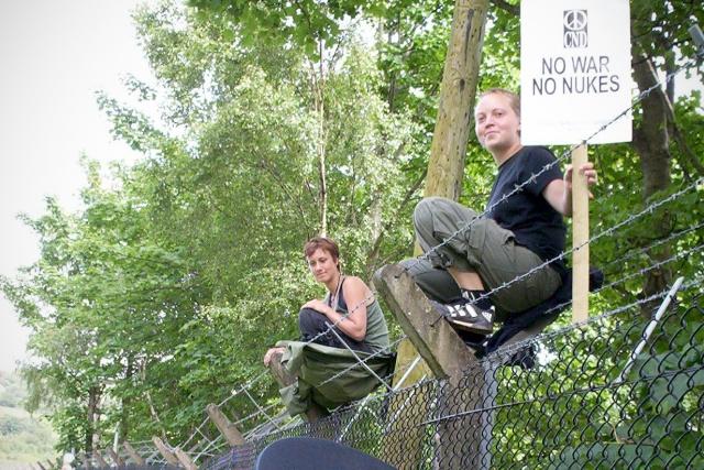 2 personer sitter på taggtrådsförsett stängsel ovanför folkmassa