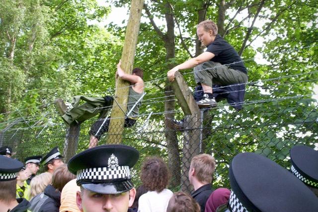 2 personer klättrar ned på andra sidan ett taggtrådsförsett stängsel, ovanför folkmassa
