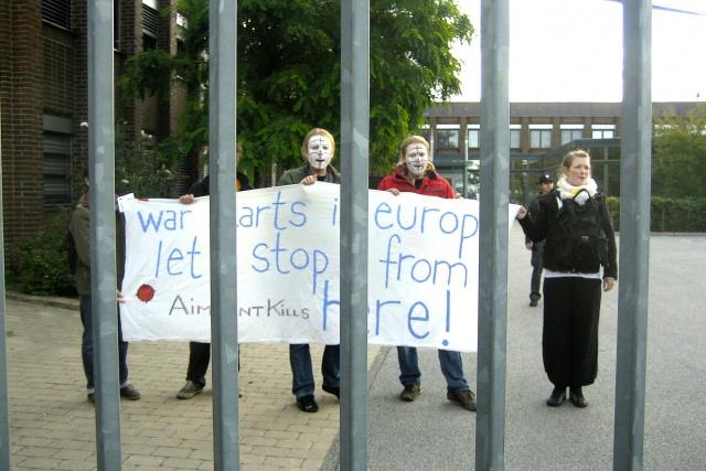 4 personer står innanför Aimpints grindar och håller upp en banderoll med texten: War Starts in Europe - Lets stop it from here!