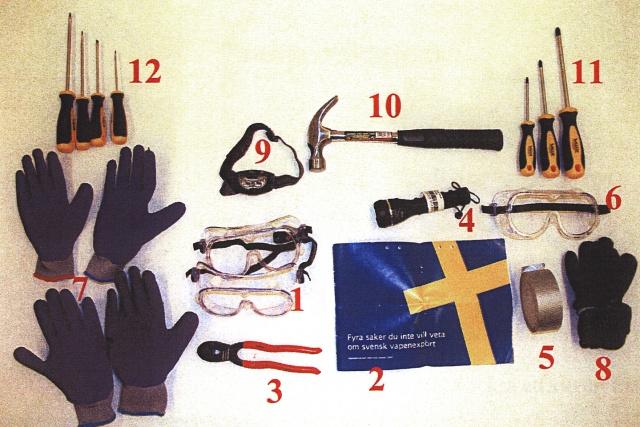 En samling av saker: Bland annat handskar, hammare, skyddsglasögon, tång, tejp, ficklampa, skruvmejsel, faktabroschyr om vapen.
