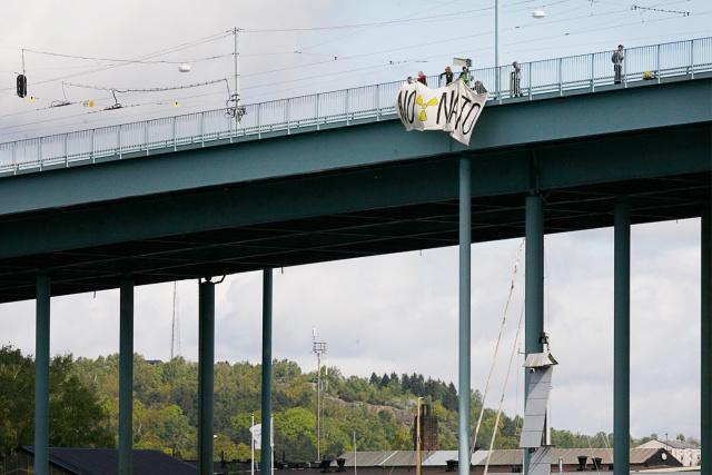 """En banderoll med texten """"No Nato"""" hängs från en bro"""