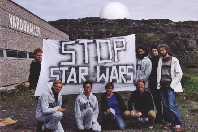 """Gruppbild framför Vardöbasen med en banderoll: """"Stop Star Wars""""."""