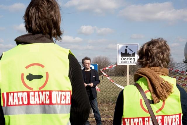 """Tre personer står framför basen. Två har västar logotypen på. En skylt säger: """"Oorlog begint hier"""""""