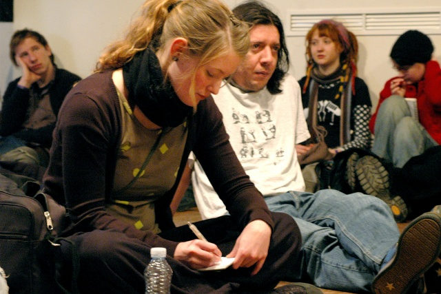 En grupp personer sitter på ett golv och lyssnar. En person skriver i ett block.