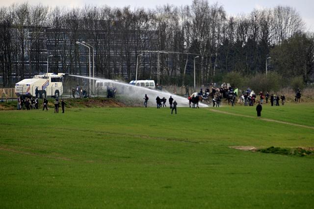 En vattenkanon sprutar vatten på demonstranter vid ett högt stängsel.