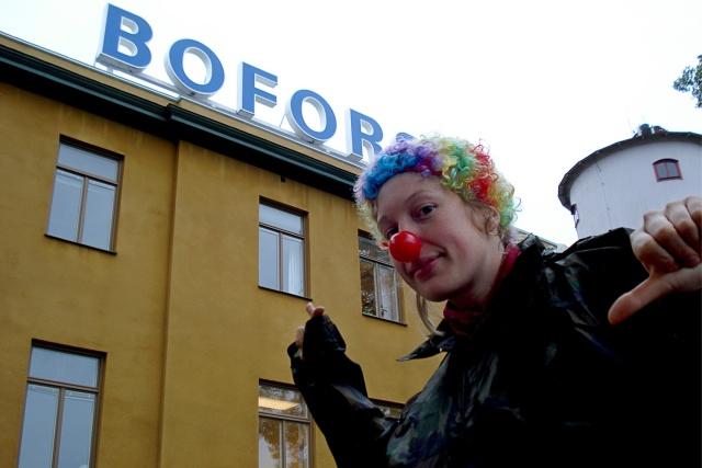 En clown pekar på en bofors-skylt ovanpå ett gult hus