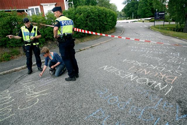 En person skriver länders namn på asfalten. Två poliser står bredvid