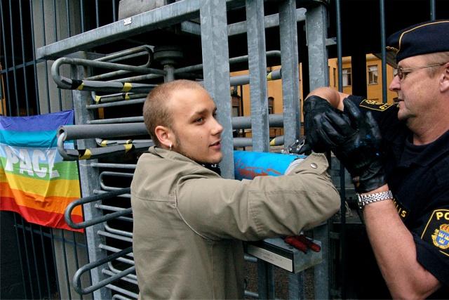 En person är fastlåst i en gallergrind och pratar med en polis.