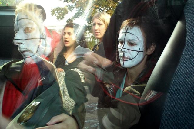 Clownsminkade aktivister reflekteras i en bilruta