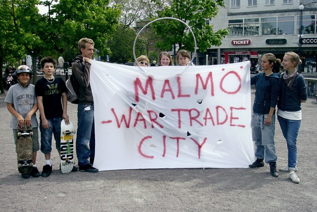 "8 personer med banderoll ""Malmö: War Trade City"""