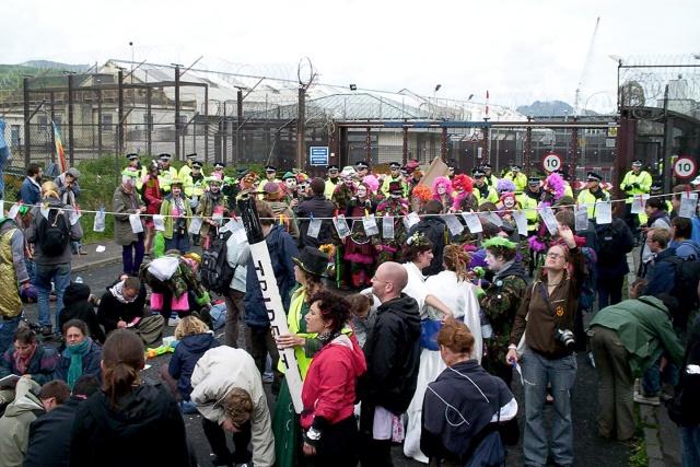 Folksamling framför ett högt stängsel