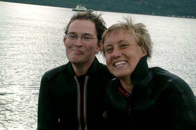 Två leende personer i våtdräkter på en strand
