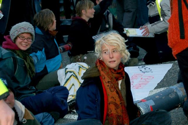 Flera personer sitter på marken med armarna instuckna i rör