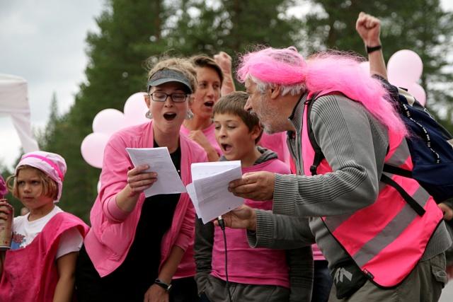 Rosaklädda demonstranter sjunger.