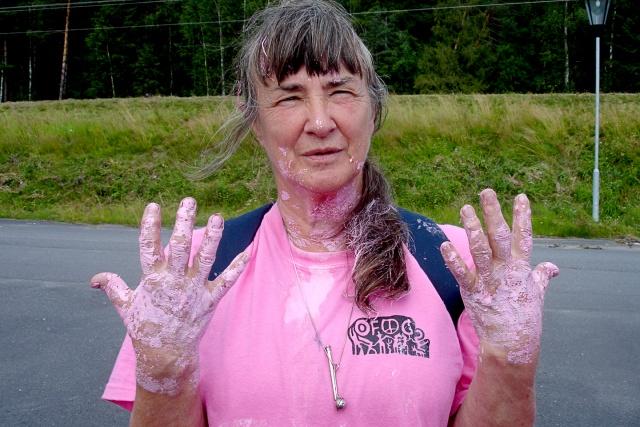 En kvinna i rosa t-shirt med rosa färg på händerna
