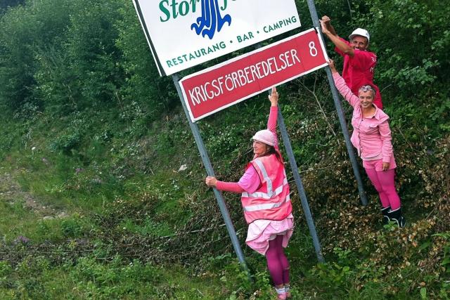 """Rosaklädda demonstranter sätter upp en rosa vägskylt """"Krigsförberedelser 8"""""""
