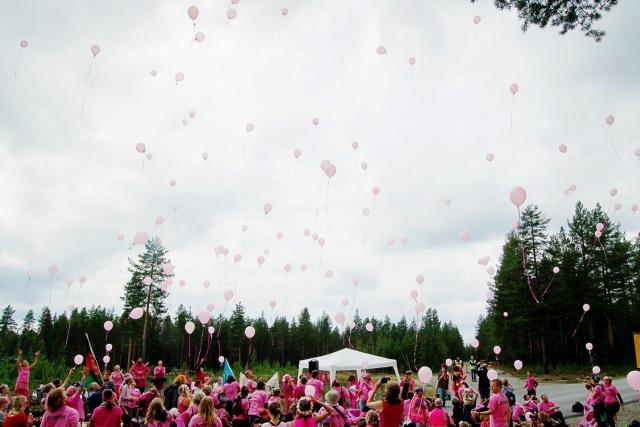 Rosaklädda människor släpper rosa ballonger över Neat