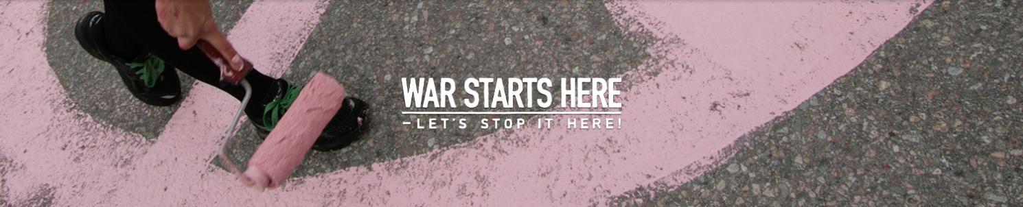 En roller målar rosa fredstecken på asfalt. War Starts Here's logotyp.