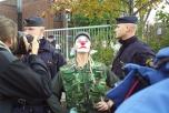 Clown posar för kameran mellan två poliser. Fotograf tar bild.