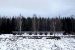 En låg, brun och vit byggnad mellan en snötäckt åker och en mörk skog