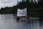 """Bild på kanoter med banderoll """"Neutralitet på drift"""" i Lule älv"""