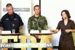 Två manliga soldater och en civilklädd kvinna står på en scen