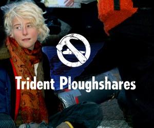 En ung person blockerar en väg. Trident Ploughshares logotyp, med en ubåt och en hammare.